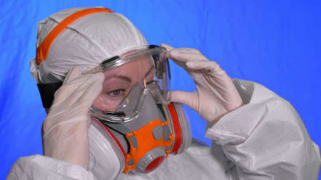 Scientist virologist in respirator. Woman close up look, wearing protective medical mask. Concept health safety N1H1 epidemic 2019 nCoV. Foto de archivo