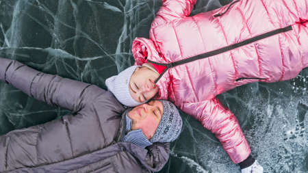 Couple has fun during winter walk against background of ice of f