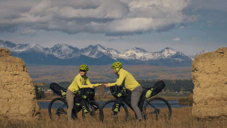 The man and woman travel on mixed terrain cycle touring with bikepacking. The two people journey with bicycle bags. Mountain snow capped, stone arch.
