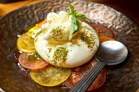 a mozzarella cheese dish sprinkled with herbs and around tomatoes nice