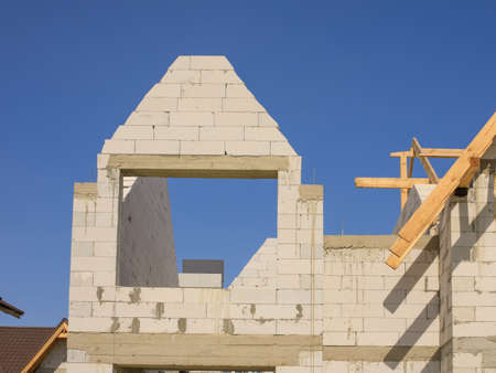 small construction of a house, with white bricks or foam block, against the background of the sky
