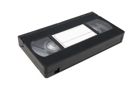 videocassette: Videocasete negro que hay sobre un fondo blanco con una etiqueta para las inscripciones. Foto de archivo