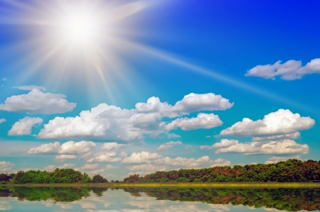The big smooth surface of water lake and gaze  Behind lake wood and the bright day sun over wood  photo