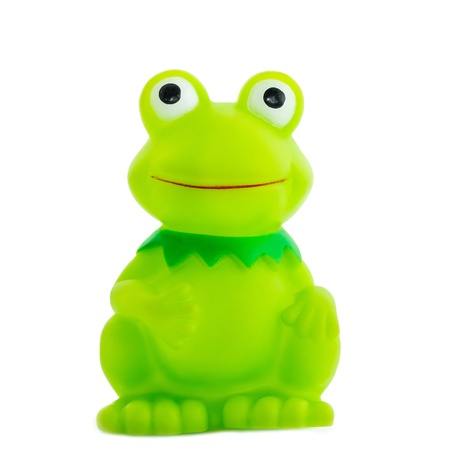 The plastic toy, cheerful green frog smiles, is isolated on a white background