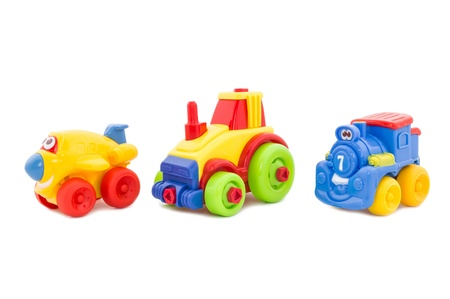 On a white background there are three plastic bright toys on wheels - the plane, a tractor and a steam locomotive. photo