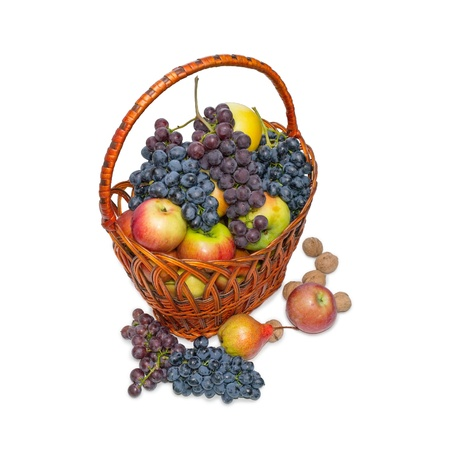 Fruit in a wattled basket on a white background. Apples, grapes, pears, nuts. photo