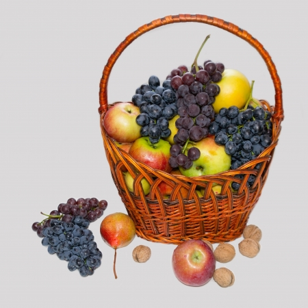 Fruit in a wattled basket on a grey background  Apples, grapes, pears, nuts Stock Photo - 15178653