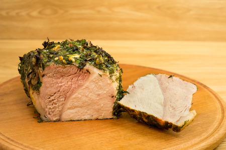 potherb: The pork fillet baked in potherb in a wind case is cut on a round board.