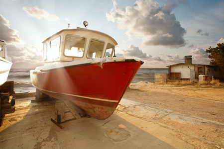 navigating: The boat in the parking lot on the background of a beautiful sunset over the sea Stock Photo