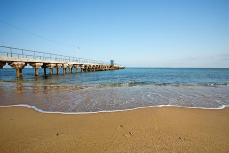 Sandy beach with a pier photo