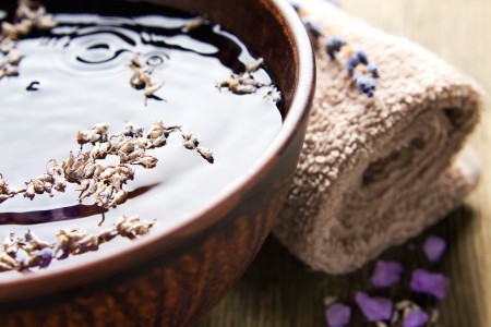 Bowl of pure water and lavender petals on the old wooden surface  Spa treatments composition