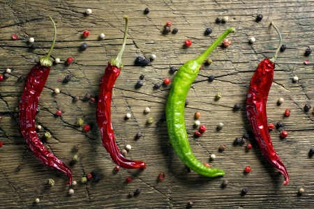 Red and green chili peppers and pepper mix on vintage wooden table background photo