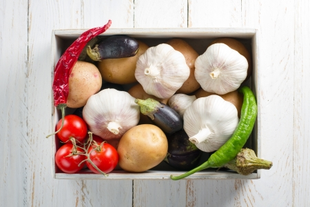 Some vegetables in wooden box on vintage wooden table. Garlic, Potato, Chili Pepper, Tomato, Eggplant photo