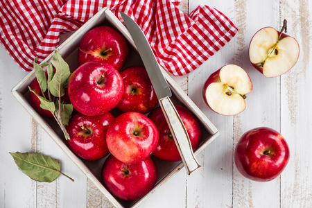 juicy: red apples on white wooden table top view