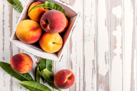 fresh peaches with leaves on white wooden table top view Stok Fotoğraf - 61699438
