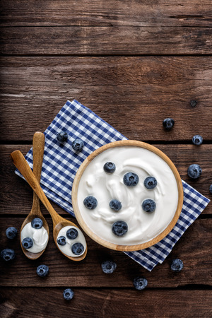blueberry yogurt in a bowl on wooden table top view