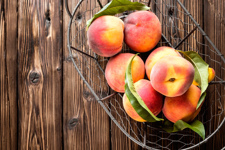 fresh peaches with leaves on white wooden table top view
