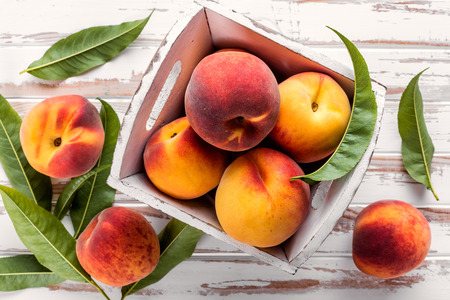 fresh peaches with leaves on white wooden table top view Reklamní fotografie - 61699454