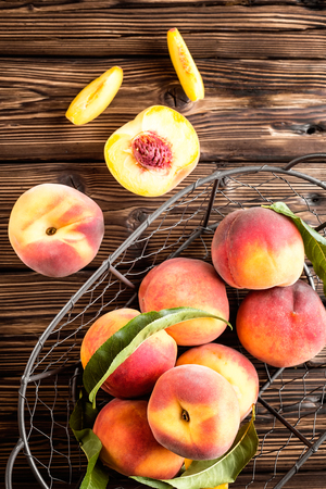durazno: fresh peaches with leaves on white wooden table top view