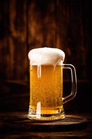 glass of fresh beer on a dark wooden background