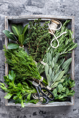 fresh herbs in wooden box on stone background Imagens