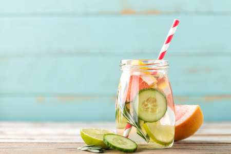 infused detox water with lime, grapefruit, cucumber and rosemary for diet healthy eating and fat burning with space for a text