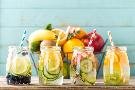 Variety of fruit infused detox water in glass jars for a healthy diet eating