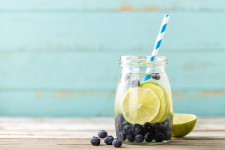 infused detox water with lime and blueberry for diet healthy eating and fat burning with space for a text