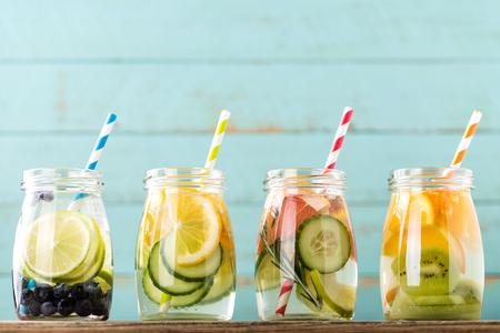 Verscheidenheid van fruit gegoten detox water in potten voor een gezond dieet eten