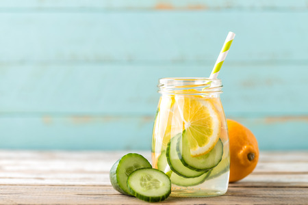 infused detox water with cucumber and lemon for diet healthy eating and fat burning with space for a text