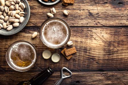 갈색 나무 테이블, 상위 뷰 및 텍스트를위한 공간에 신선한 맥주와 짠 스낵의 두 잔
