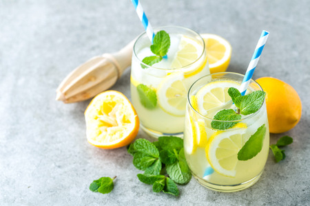 Lemonade or mojito cocktail with lemon and mint, cold refreshing drink or beverage with ice Фото со стока