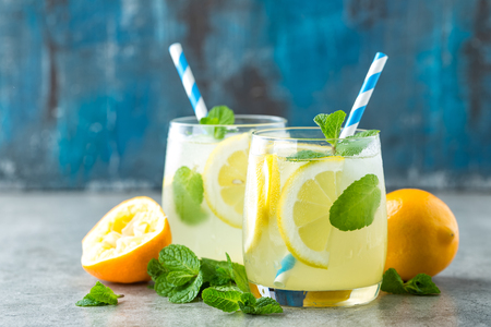 Lemonade or mojito cocktail with lemon and mint, cold refreshing drink or beverage with ice Stock Photo
