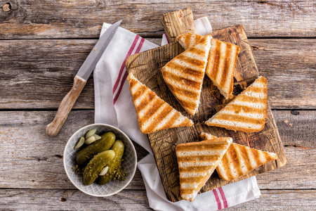 hot toasted sandwich panini with ham and cheese on wooden cutting board