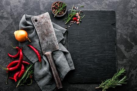 dunkler kulinarischer Hintergrund mit leerem schwarzem Schieferbrett und Raum für Textrezept oder Fleischmenü