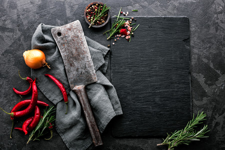 dark culinary background with empty black slate board and space for text recipe or meat menu