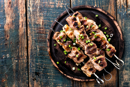 Grilled meat skewers, shish kebab on wooden background, top view Imagens