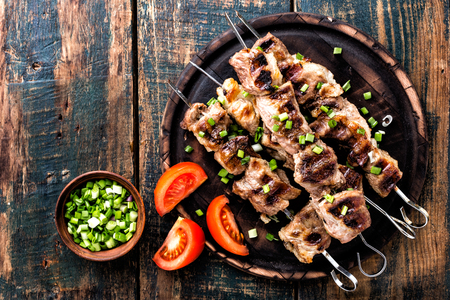 Grilled meat skewers, shish kebab on wooden background, top view Stockfoto