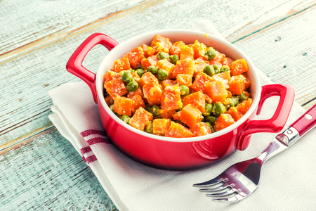 Carrot braised with fresh green peas in creamy milk sauce in stewpan, stewed vegetable saute