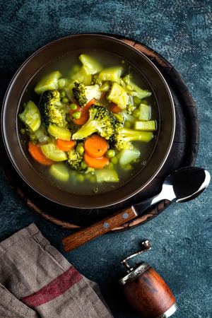 plate of fresh hot vegetable soup with broccoli, potato, green peas, onion and carrot. healthy vegan diet food, top view Stock Photo