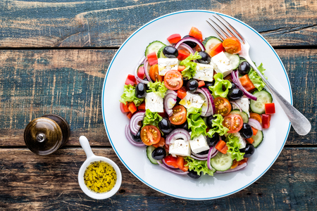 Greek salad of fresh cucumber, tomato, sweet pepper, lettuce, red onion, feta cheese and olives with olive oil. Healthy food, top view Stockfoto