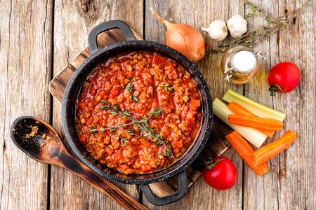 klassieke Italiaanse bolognese saus gestoofd in ketel met ingrediënten op houten tafel, bovenaanzicht