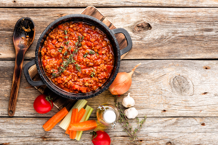 classic italian bolognese sauce stewed in cauldron with ingredients on wooden table, top view, culinary background with space for text Banco de Imagens