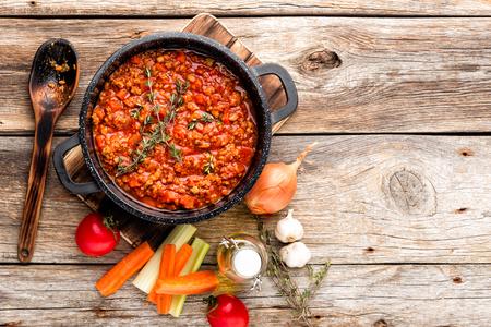 klassieke Italiaanse bolognese saus gestoofd in ketel met ingrediënten op houten tafel, bovenaanzicht, culinaire achtergrond met ruimte voor tekst