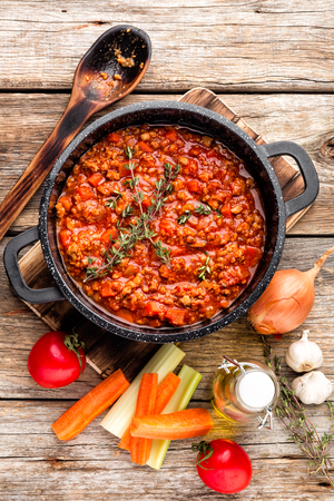classic italian bolognese sauce stewed in cauldron with ingredients on wooden table, top view Stock Photo - 97016635