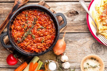 classic italian bolognese sauce stewed in cauldron with ingredients on wooden table, top view Stock Photo - 97442528