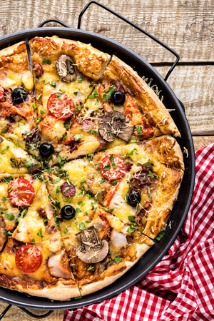 pizza with cheese, tomatoes, mushrooms, ham, sausage and olives on a wooden table, top view