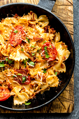 pasta farfalle with roasted meat and tomatoes in a frying pan