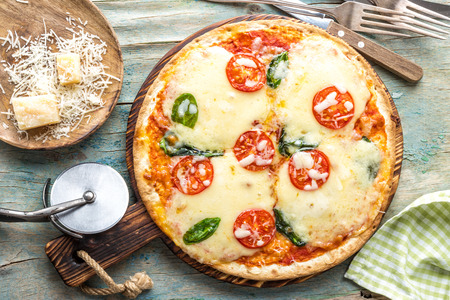 pizza margarita top view on a rustic wooden table, Margherita  cooked according to the traditional recipe of Italian cuisine Reklamní fotografie