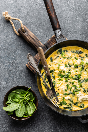 omelette with spinach and cheese in a pan on the concrete background top view Stock Photo